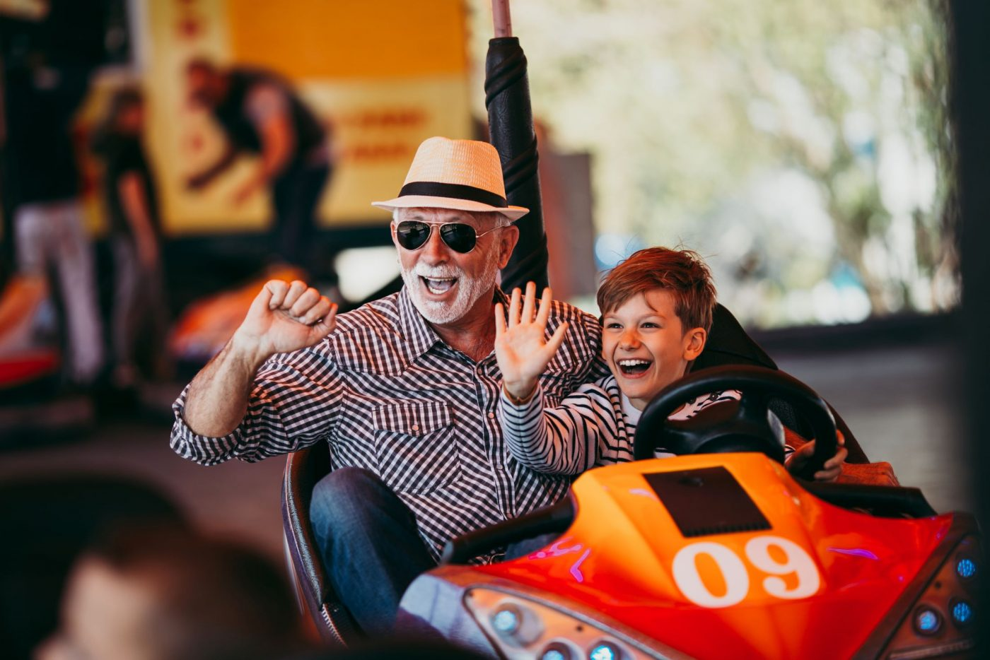 grampa and grandson playing in a bumper car happy and waving at family. Safe while having fun.