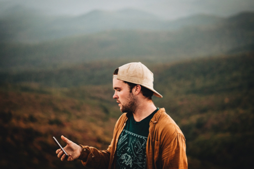 Guy in the mountains checking his account on his phone