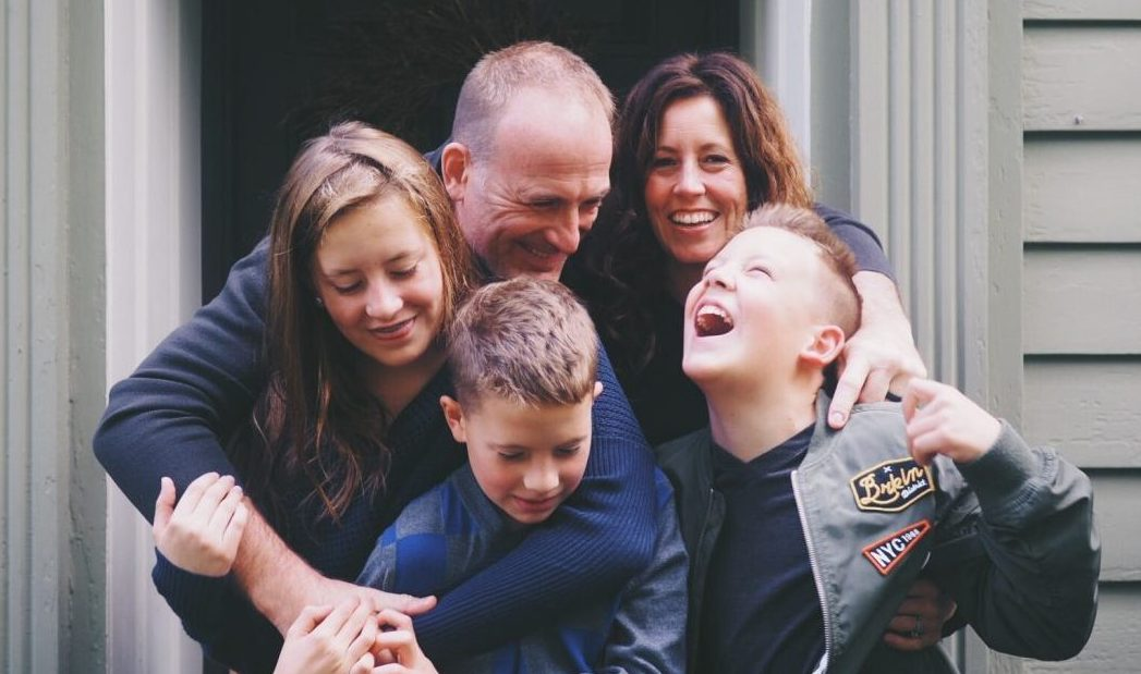 family laughing and hugging in front of their home
