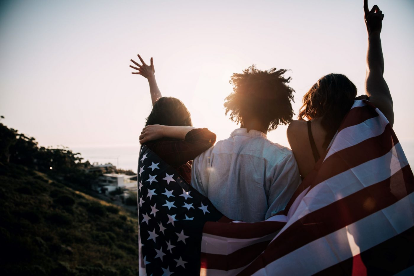 group of friends looking at the sunset with a the flag wrapped around them and arms in the air celebrating