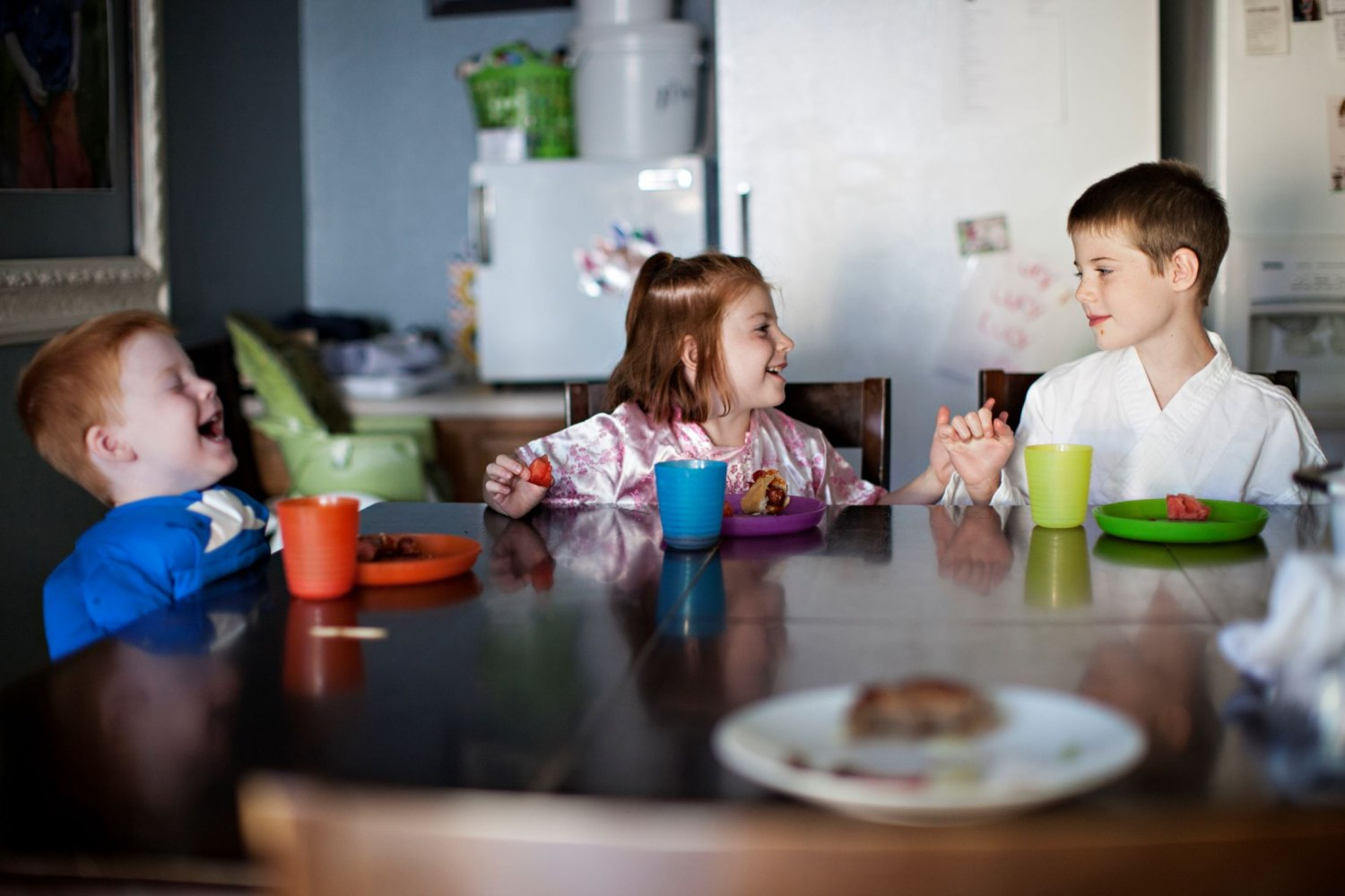 kids at a dining room table talking and smiling