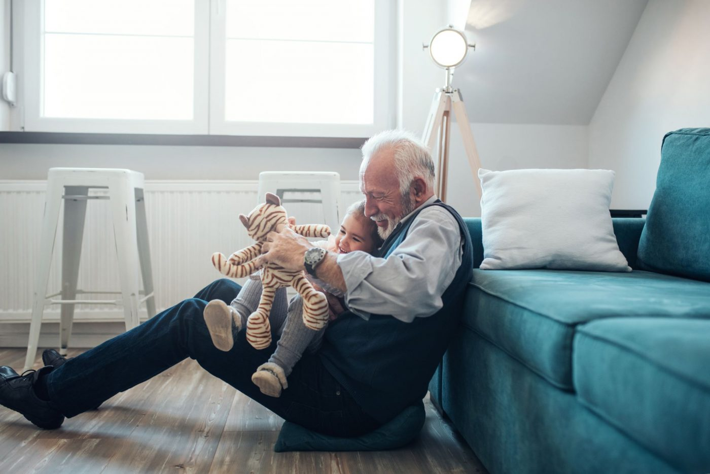 Grampa and toddler playign with a toy tiger on the floor