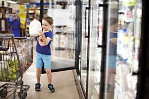 little boy adding milk to the grocery cart