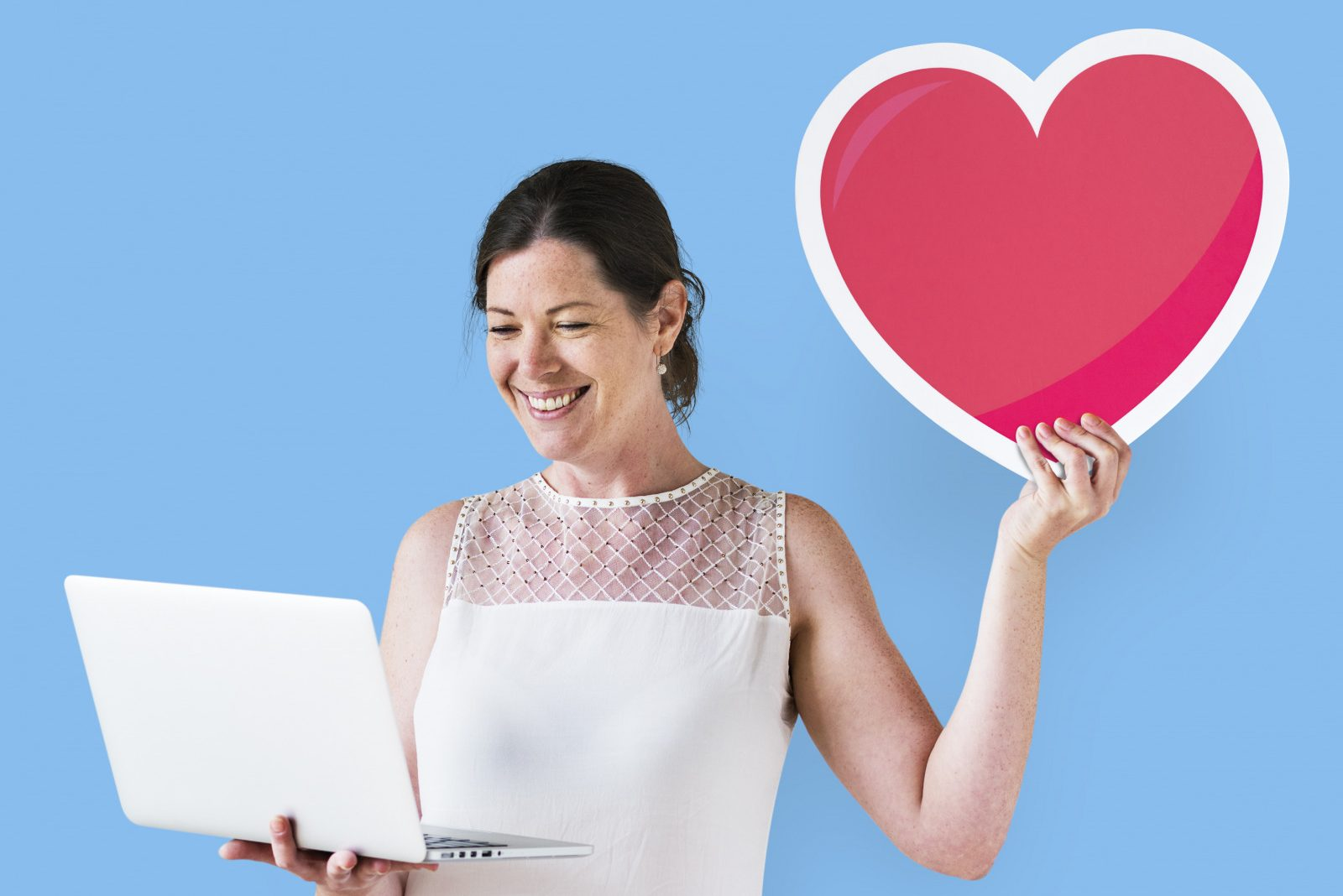 woman on a laptop requesting a donation holding a large paper heart in her hand